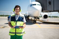 Male worker in headphones holding clipboard and smiling royalty free stock image
