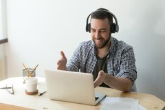 Smiling worker in headphones talking at laptop via video call. Male worker in headphones talking, making video call, chatting with friend or consulting client Stock Photos