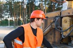 Male worker in helmet. Looking at excavator Stock Photo