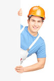 A male worker with helmet posing behind a blank panel Royalty Free Stock Photography