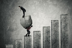 Male worker and his leader with stone. Image of a male worker climbing a stairs while carrying a big stone with his leader standing on the stone Royalty Free Stock Images