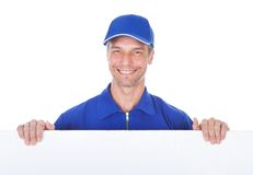 Male worker holding blank placard. Happy Mature Male Worker In Dungaree Holding Blank Placard Stock Image