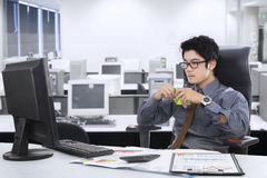 Male worker holding coffee in the office. Young asian businessman sitting on the chair while enjoy a cup of coffee in the workplace Stock Photos
