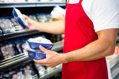 Male worker holding mushroom. In grocery store Stock Photo
