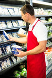 Male worker holding mushroom. In grocery store Stock Photography