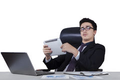Male worker holding a tablet at desk Stock Images
