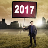 Male worker holds 2017 outdoors. Image of a young male worker holding a billboard with number 2017 and standing on the meadow Stock Photography