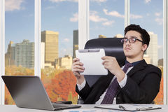 Male worker holds tablet while sitting in office Royalty Free Stock Photography