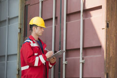 Male worker inspecting cargo container while writing on clipboard in shipping yard Stock Photo