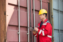Male worker inspecting cargo container while writing on clipboard in shipping yard Stock Image