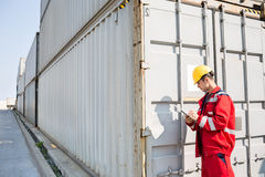 Male worker inspecting cargo container while writing on clipboard in shipping yard Royalty Free Stock Image