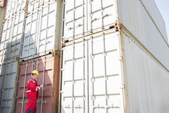 Male worker inspecting cargo containers while writing on clipboard in shipping yard Royalty Free Stock Photos