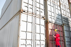 Male worker inspecting cargo containers while writing on clipboard in shipping yard Royalty Free Stock Image