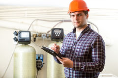 Male worker inspecting work of industrial equipment Stock Image
