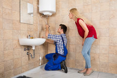 Male Worker Installing Electric Boiler With Screwdriver. Young Woman Looking At Male Worker Installing Electric Boiler At Bathroom royalty free stock photos