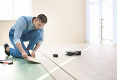 Male worker installing flooring. Male worker installing laminate flooring Stock Photos