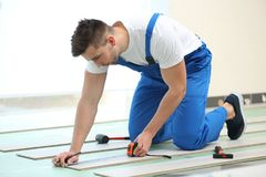 Male worker installing laminate. Flooring Royalty Free Stock Images