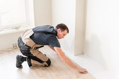 Male worker installing new wooden laminate flooring. The combination of wood panels of laminate and ceramic tiles in the stock image