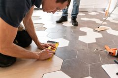 Male worker installing new wooden laminate flooring. The combination of wood panels of laminate and ceramic tiles in the stock photos
