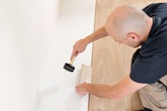 Male worker installing new wooden laminate flooring on a warm film foil floor. infrared floor heating system under. Laminate floor stock image