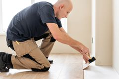 Male worker installing new wooden laminate flooring on a warm film foil floor. infrared floor heating system under. Laminate floor royalty free stock photos