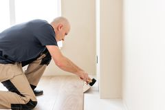 Male worker installing new wooden laminate flooring on a warm film foil floor. infrared floor heating system under. Laminate floor royalty free stock images