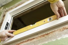 The male worker installs UPVS the window using the level. The male worker installs UPVS a window ine the premises using a level royalty free stock photos