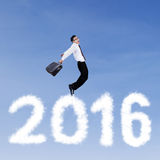 Male worker jumping above numbers 2016. Image of happy young businessman jumping on the sky above clouds shaped numbers 2016 Stock Image