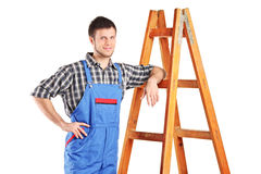 Male worker in jumpsuit standing next to a ladder. Isolated on white background Royalty Free Stock Images