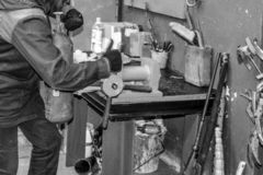 A male worker on a large metal industrial vice is repairing a red fire extinguisher cylinder in a workshop at the plant royalty free stock photography