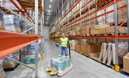 Male worker with loader and clipboard at warehouse. Logistic business, shipment and loading concept - male worker with loader and clipboard at warehouse Stock Photography