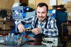 Male worker making hole in belt in specialized workshop Stock Images