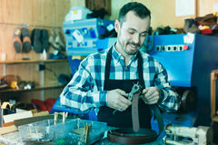 Male worker making hole in belt in specialized workshop Royalty Free Stock Photo