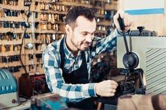 Male worker making key in specialized workshop. Young diligent friendly male worker making key in specialized workshop Stock Image