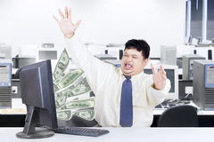 Male worker with money from computer. Successful businessman get money from internet while working in the office Stock Image