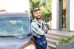 Male worker near car. Outdoors Stock Photo