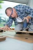 Male worker nstalling laminate flooring. Cutting Stock Photos
