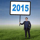 Male worker with number 2015 at field. Young businessman standing at field while holding a board with number 2015 Royalty Free Stock Photography