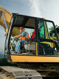 Male worker operating excavator. On construction site Royalty Free Stock Photos