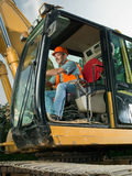 Male worker operating excavator. Happy male worker operating excavator on construction site Stock Photography