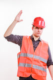 Male worker in orange uniform with hand up. Job and work concept. Young male worker wearing safety vest and hard hat holding hand up. Repairman inspector at Stock Photos