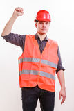 Male worker in orange uniform with hand up. Job and work concept. Young male worker wearing safety vest and hard hat hand up. Repairman inspector at work Royalty Free Stock Photo