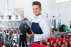Male worker packaging wine bottles at sparkling wine factory Royalty Free Stock Image