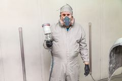 A male worker painting a car is standing in a spray booth in protective clothing with a spray gun in his hands pointing forward stock images