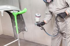 A male worker paints with a spray gun a part of the car body in silver after being damaged at an accident. Bumper from the vehicle stock photo