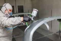 A male worker paints with a spray gun a part of the car body in silver after being damaged at an accident. Plastic elements from royalty free stock photography