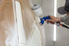 A male worker paints with a spray gun a part of the car body in white after being damaged at an accident. Door from the vehicle stock image