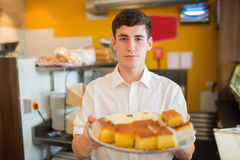 Male worker with pastries in bakery. Portrait of male worker with pastries standing in bakery Royalty Free Stock Photography
