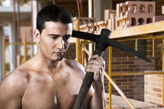 Male worker with pick axe and bricks Royalty Free Stock Photos