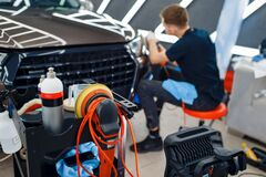 Male worker polishes headlights, car detailing